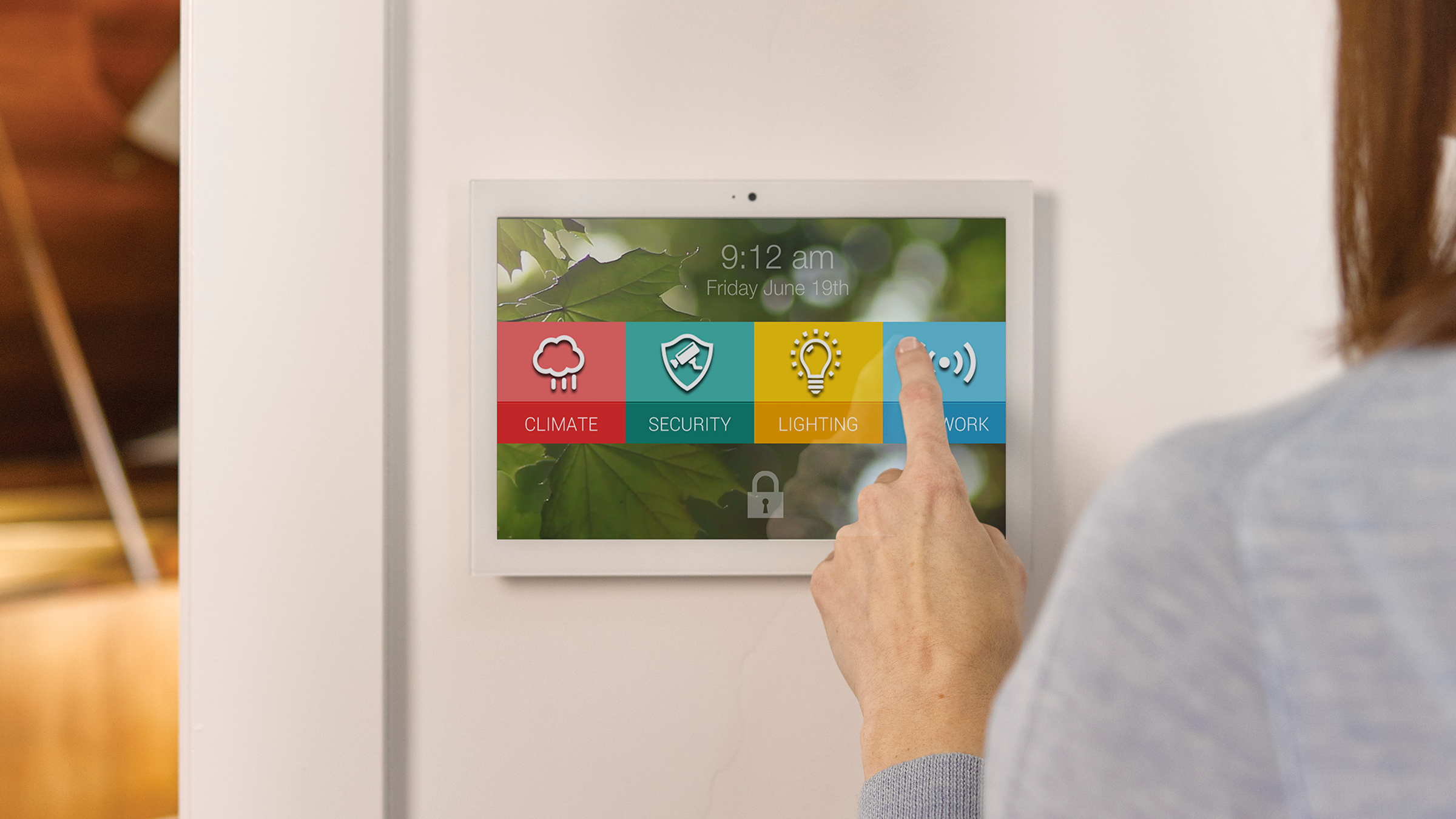 Person using a smart home touch screen UI mounted on a wall