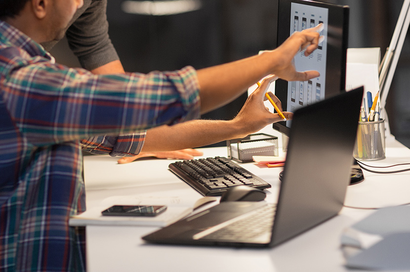 Designers collaborate as they look at a computer